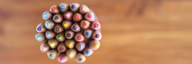 Wiele wielobarwnych ołówków na drewnianym tle widok z góry sprzedaż koncepcji papeterii
