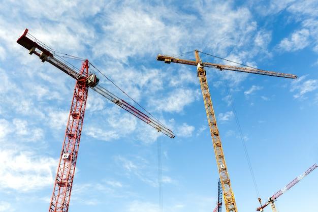 Wiele wysokich żurawi wieżowych pracuje nad budową nowych budynków. szeroki kąt.
