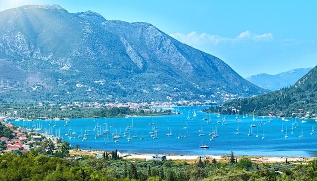 Wiele żaglowców w zatoce. zamglone lato panorama wybrzeża lefkady (nydri, grecja, morze jońskie).