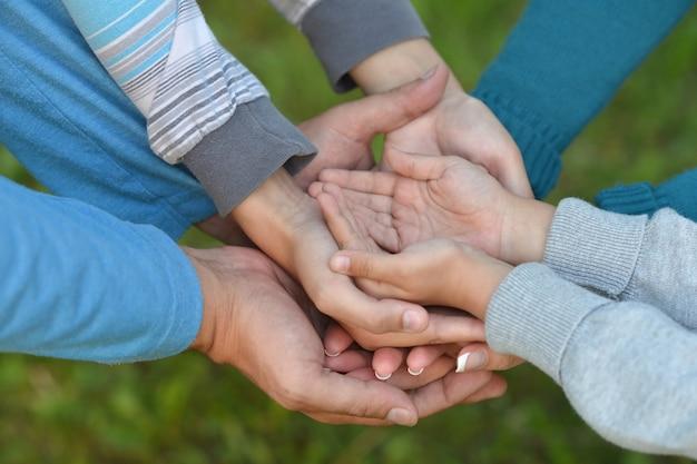 Wiele zjednoczonych rąk na zielonym tle z bliska