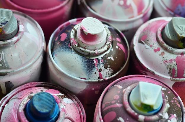 Wiele zużytych puszek z farbą w zbliżeniu. brudne i rozmazane puszki do rysowania graffiti.