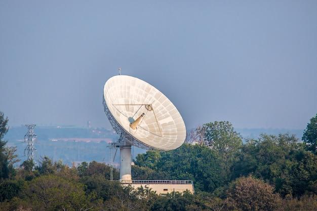 Wielka antena satelitarna na lesie nad chmurniejącym tłem
