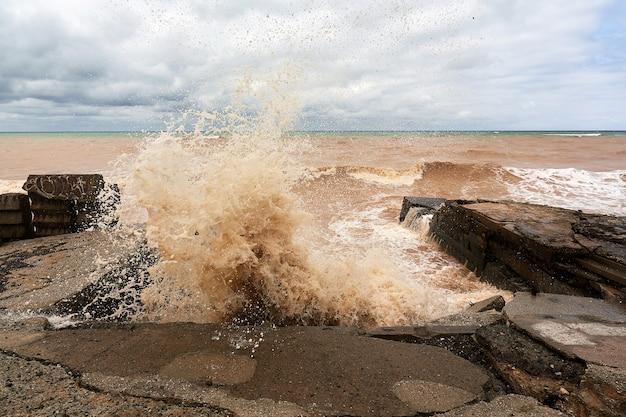 Wielka fala morska z rozbryzgami rozbija się o kamienny falochron