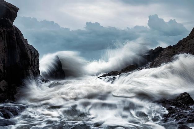Wielka fala uderzająca w skały na wybrzeżu podczas burzy na tropikalnym morzu