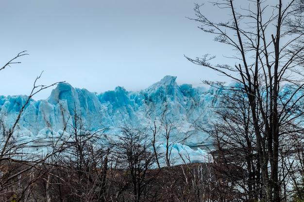 Wielka góra lodowa w wodzie z mglistym niebem