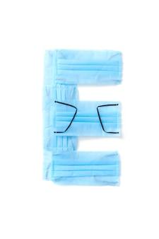 Wielka litera e wykonana ręcznie z medycznych antybakteryjnych ochronnych niebieskich masek na białej ścianie, miejsce na kopię. kreatywny alfabet do tworzenia nowych słów.