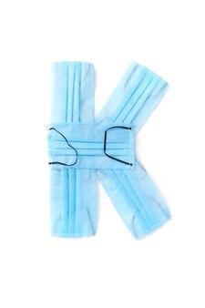Wielka litera k wykonana ręcznie z medycznych antybakteryjnych ochronnych niebieskich masek na białej ścianie, miejsce na kopię. kreatywny alfabet do tworzenia nowych słów.