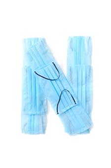 Wielka litera n wykonana ręcznie z medycznych antybakteryjnych ochronnych niebieskich masek na białej ścianie, miejsce na kopię. kreatywny alfabet do tworzenia nowych słów.