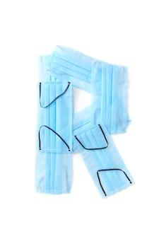 Wielka litera r wykonana ręcznie z medycznych antybakteryjnych ochronnych niebieskich masek na białej ścianie, miejsce na kopię. kreatywny alfabet do tworzenia nowych słów.