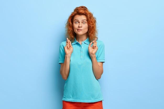 Wielka nadzieja na lepsze. rudowłosa zaskoczona młoda kobieta krzyżuje palce, robi modlący się gest, ubrana w swobodne letnie ubrania
