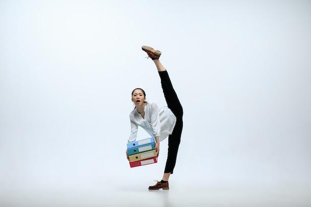 Wielka odpowiedzialność. cierpiąca kobieta pracująca w biurze, skacząca i tańcząca w ubranie lub garnitur na białym tle na tle białego studia. biznes, start-up, praca w koncepcji otwartej przestrzeni.