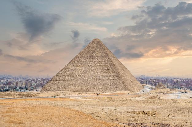 Wielka piramida cheopsa w kairze. egipskie piramidy w gizie na tle kairu. cud światła. zabytek architektury. groby faraonów. wakacje wakacje w tle