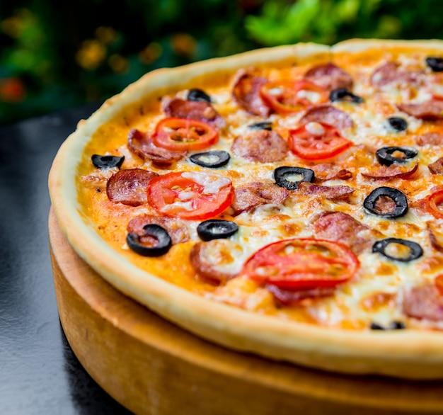 Wielka pizza na drewnianym stole.