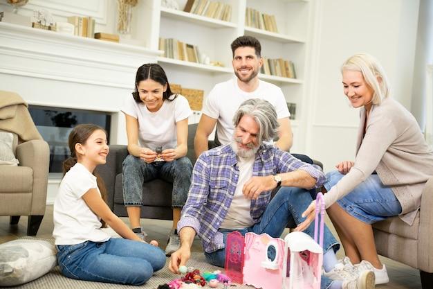 Wielka szczęśliwa wielopokoleniowa rodzina bawiąca się z uroczym dzieckiem w salonie w domu