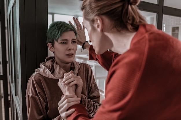 Wielka walka. młoda zielonowłosa kobieta boi się swojego chłopaka podczas wielkiej kłótni
