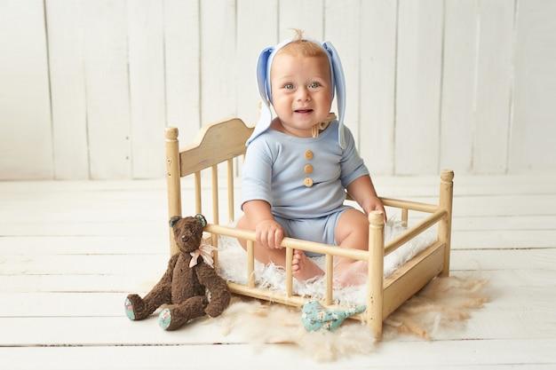Wielkanoc chłopiec siedzi na łóżeczku. zajączek wielkanocny. szczęśliwe dziecko