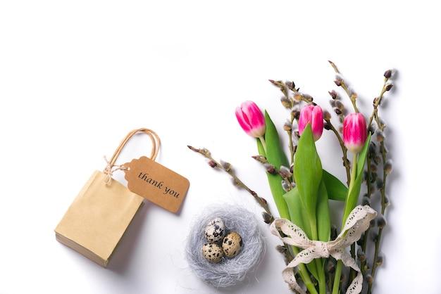 Wielkanoc na białym tle z przepiórczymi jajami w gnieździe i tulipany z gałązką wierzby i pudełko z tagiem dziękuję. wolne miejsce na tekst.