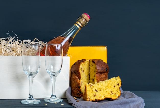 Wielkanoc panetone włoski z butelką szampana i dwie szklanki na niebieskim tle.
