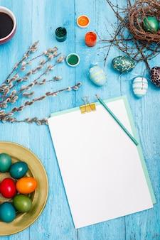 Wielkanoc w biurze pracy na niebieskim drewnianym stole.