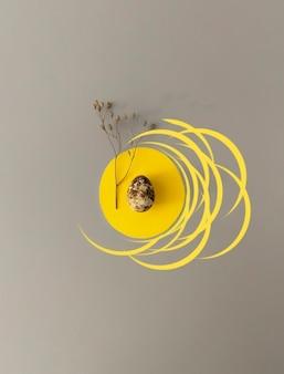 Wielkanoc w modnych kolorach. jajka przepiórcze z suszonymi kwiatami na żółtym i szarym tle z miejsca na kopię.