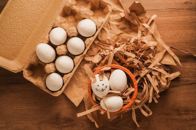 Wielkanoc, zdobione jajko jak twarz królika i białe jajka na brązowym papierze oraz w tacy na jajka na drewnianym stole