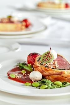 Wielkanocna bułka mięsna, pieczeń na wielkanocny obiad. pięknie udekorowany cateringowy stół bankietowy z różnymi przekąskami i przystawkami.