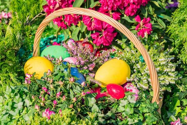 Wielkanocna dekoracja uliczna. wiklinowy kosz pełen pisanek, ciastek i kwiatów.