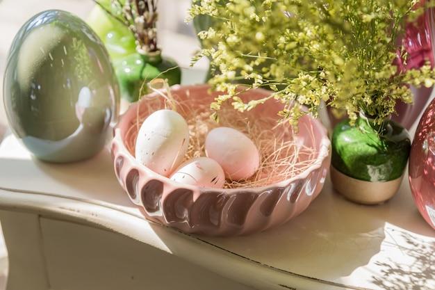 Wielkanocna dekoracja wnętrz. piękna kompozycja z gniazdem, jajami i kwitnącymi kwiatami.