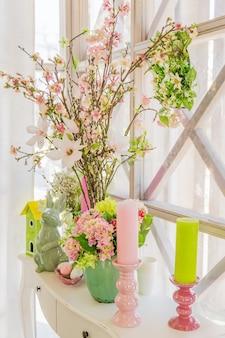 Wielkanocna dekoracja wnętrz. piękna kompozycja ze świecami. jaja, króliki, domek dla ptaków i kwitnące gałęzie jabłek.