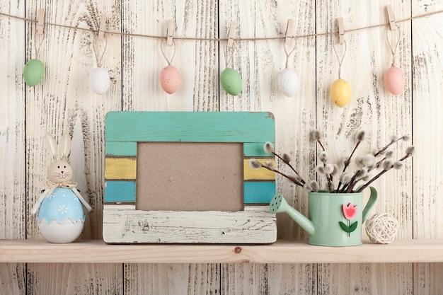Wielkanocna dekoracja z pustą drewnianą ramą na półce