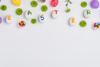 Wielkanocna inskrypcja na jajkach z kwiatami na stole