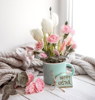 Wielkanocna kompozycja kwiatowa z naturalnymi kwiatami i napisem wesołych świąt na karcie.