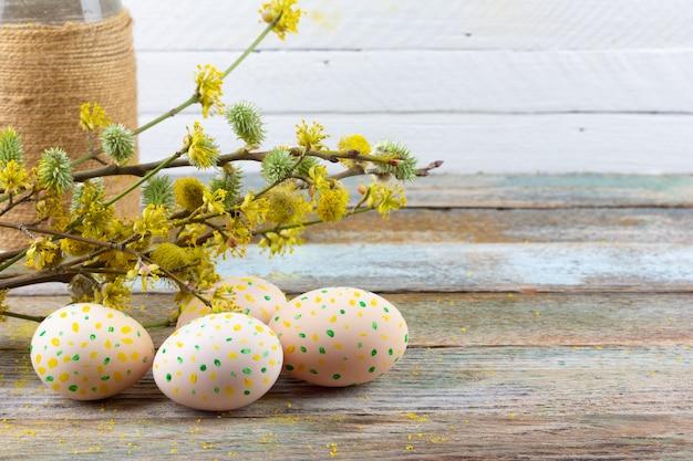 Wielkanocna kompozycja kwitnących gałązek wierzby, derenia i pisanek z wzorem żółtych kropek na drewnianym tle retro z kopią zbliżenia kosmicznego