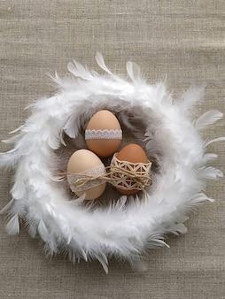 Wielkanocna kompozycja ozdobiona koronką pisanki w biały wieniec z piór na lnianym tle. koncepcja bez plastiku i zero odpadów