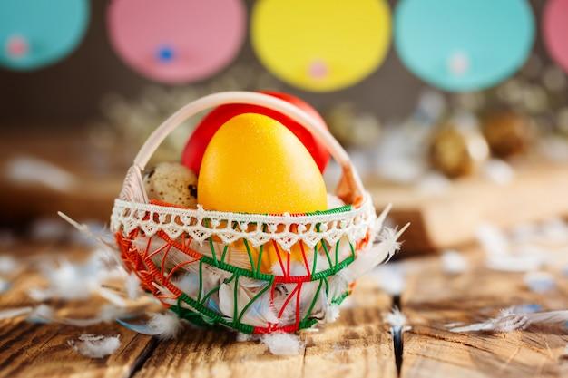 Wielkanocna kompozycja pisanek kolorowych w koszyku i z girlandą króliczka.