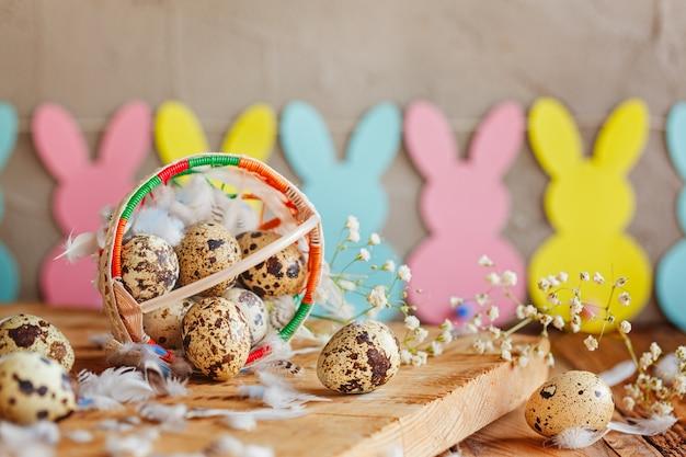 Wielkanocna kompozycja pisanek przepiórczych w koszyku i z girlandą króliczka.