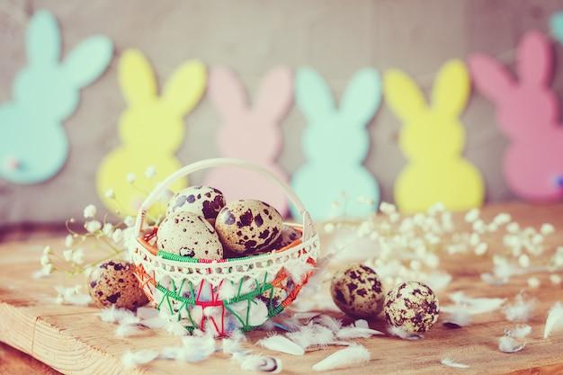 Wielkanocna kompozycja pisanek przepiórczych w koszyku z girlandą króliczka.