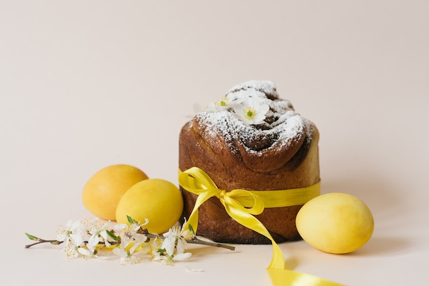 Wielkanocna kompozycja słodkiego ciasta chlebowego, białych kwiatów i żółtych jajek na jasnym tle