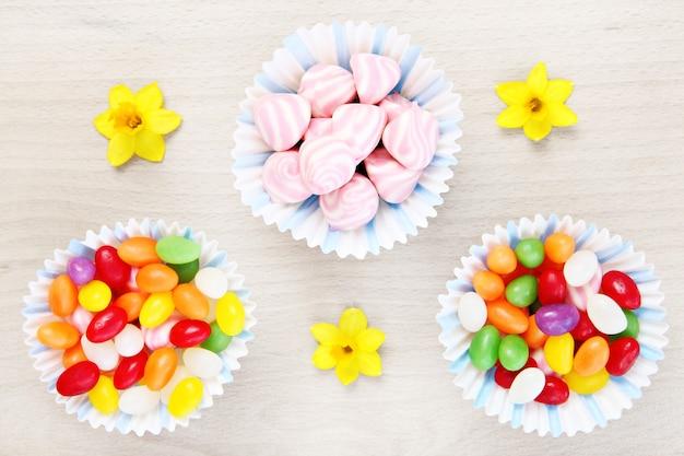 Wielkanocna kompozycja słodyczy i kwiatów na naturalnym tle