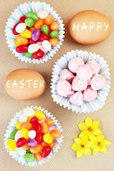 Wielkanocna kompozycja słodyczy z jajek i kwiatów na naturalnym tle
