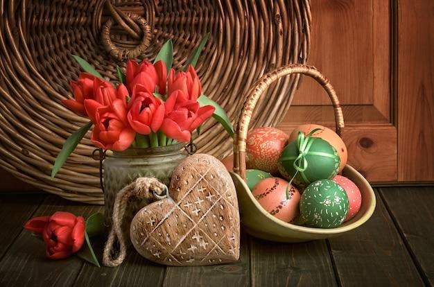 Wielkanocna kompozycja z czerwonymi tulipanami, drewnianym sercem i pisankami