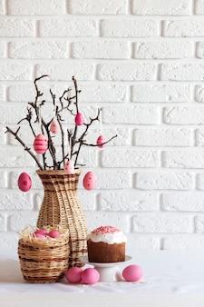 Wielkanocna kompozycja z dekorowanymi gałęziami drzew w wiklinowym wazonie, różowymi jajkami w wiklinowym koszu i wielkanocnym ciastem na białym tle. skopiuj miejsce