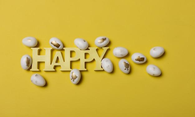 Wielkanocna kompozycja z drewnianym słowem szczęśliwy i jaja na żółtym tle z miejscem na tekst