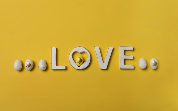 Wielkanocna kompozycja z drewnianymi słowami miłość i jajkami na żółtym tle z miejscem na tekst