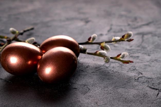Wielkanocna kompozycja z jajkami i gałązkami wierzby. minimalne tło ze złotymi pisankami na czarnym tle. skopiuj miejsce