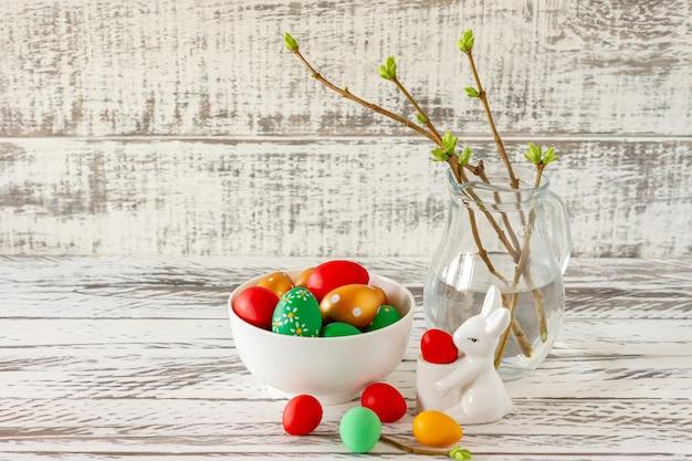 Wielkanocna kompozycja z jajkami, królikiem i wiosennymi gałązkami w szklanym słoju. wesołych świąt wielkanocnych.