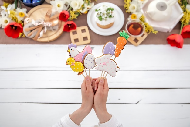 Wielkanocna kompozycja z jasnymi piernikami na patykach w kobiecych rękach. koncepcja gotowania na święta wielkanocne.