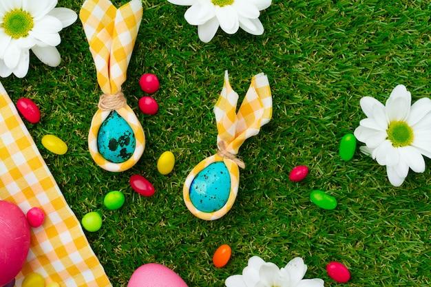 Wielkanocna kompozycja z kolorowymi jajkami i jasnymi cukierkami na żółtym obrusie