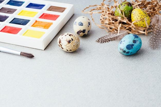 Wielkanocna kompozycja z malowanymi jajkami w koszu i farbami na szarym tle, kopia przestrzeń. tradycja wielkanocna, tło. przygotowanie do obchodów wielkanocy, koncepcja kreatywna.