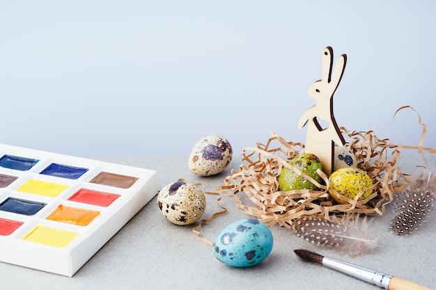 Wielkanocna kompozycja z malowanymi jajkami w koszyku, królikiem i farbami na szarym tle. tradycja wielkanocna, tło. przygotowanie do obchodów wielkanocy, koncepcja kreatywna.